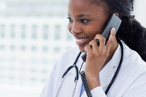 Portrait of a female doctor on the phone while using a computer