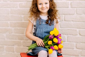 Portrait of litlle girl holding tulips bouquet