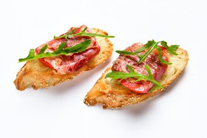 Two sandwiches with serrano ham, cheese and arugula