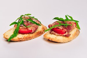 Two sandwiches with serrano ham, cheese and arugula