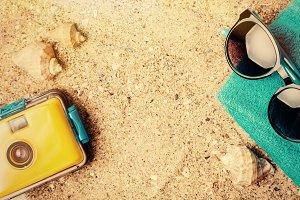 Summer accessories on sand background