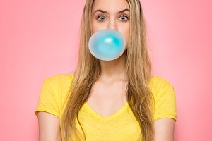 Cute girl blowing blue bubble gum
