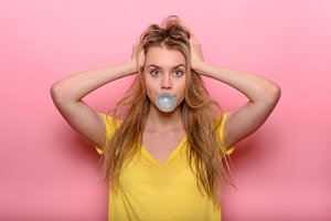 woman blowing blue bubble gum