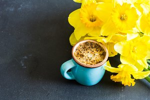 Coffee and yellow daffodils