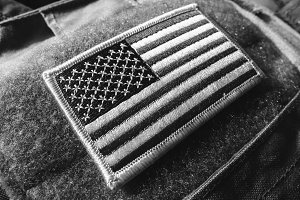 US flag velcro patch on the bulletproof vest, black and white, shallow depth of field.
