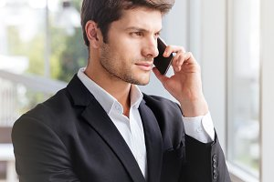 Serious young businessman talking on cell phone in office