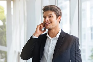 Cheerful young businessman talking on cell phone in office