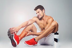 Portrait of a fitness man with foot pain