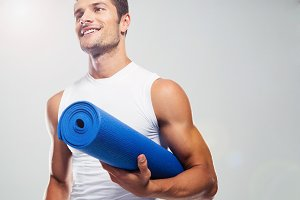 Portrait of a fitness man with yoga mat