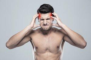 Naked man having headache
