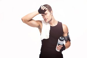 Tired fitness man with towel and bottle with water