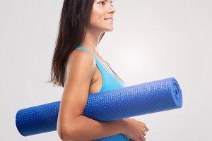 Happy sports woman holding yoga mat