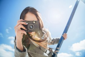Young brunette girl taking shot holding camera outdoors
