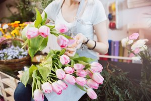 Woman florist taking care of pink tulips in flower shop