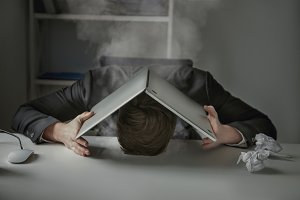 Man covers his head with laptop