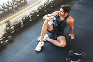 Above photo of fitness man sitting in gym