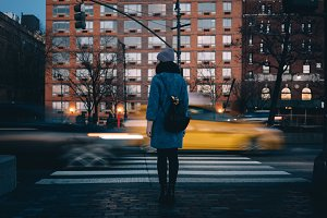 Woman with backpack waiting for green traffic light