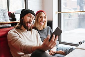 Side view of Funny Couple making selfie in cafe