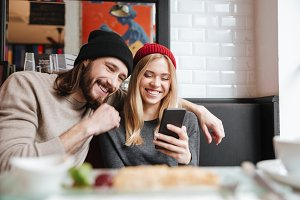 Laughing Couple looking at phone in cafe