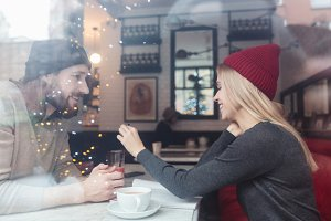 Portrait of couple in cafe behind the glass