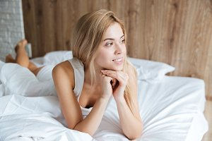 Pensive woman lying and thinking on bed in bedroom