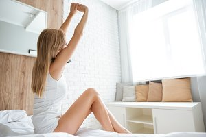Woman sitting and stretching on bed in the morning