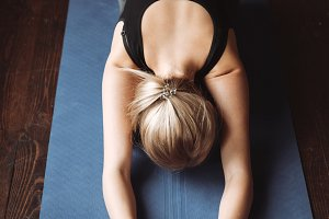 Top view of beautiful young sportswoman doing yoga exercises