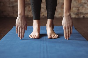 Fitness woman standing barefoot and stretching on mat