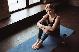Cheerful attractive young fitness woman sitting on yoga mat