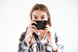 Woman holding camera over white background