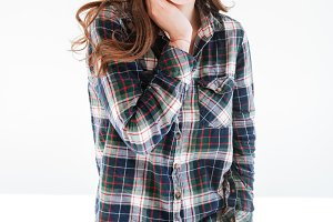 Happy charming young woman in plaid shirt standing and posing