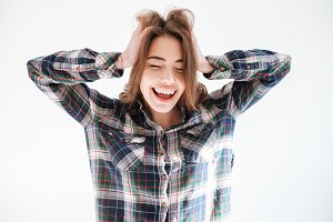 Cheerful carefree woman in plaid shirt with hands on head