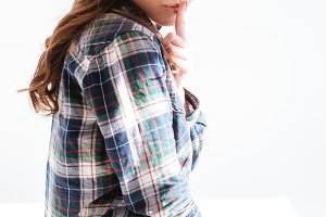 Attractive woman in plaid shirt showing silence sign and winking