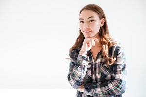 Happy young woman in plaid shirt standing with hands folded