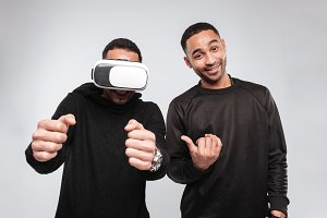 Young african men standing while using virtual reality device.