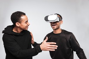 Two happy african young men using 3d virtual reality device.