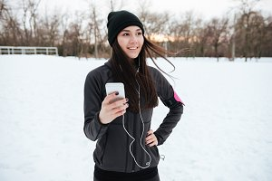 Smiling young sportswoman listening to music and jogging