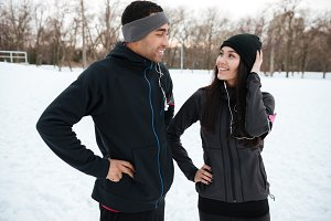 Smiling multiracial couple in sportswear laughing together outdoors