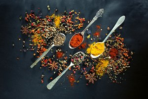 Spoons with spices on dark board