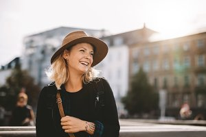 Smiling tourist woman wearing hat.