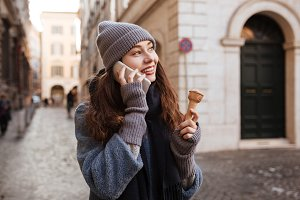 Woman with ice cream talking on mobile phone in city