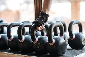 Sportswoman taking kettlebell in gym