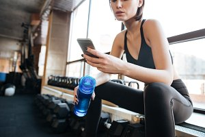 Woman athlete using cell phone in gym