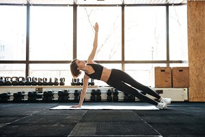Sportswoman doing exercises on mat in gym