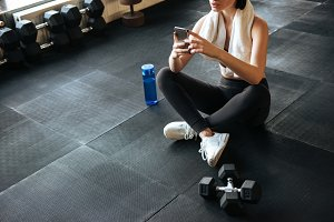 Woman athlete sitting and using mobile phone in gym