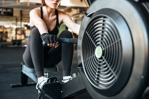 Sportswoman exercising with fitness equipment in gym
