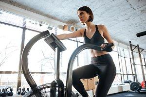 Sportswoman exercising on bike in gym