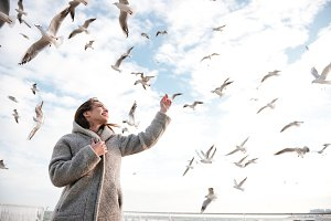 Happy woman standing and looking at seagulls in the sky