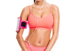 Attractive woman in sportswear listening music and looking at camera