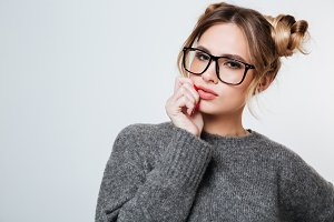 Portrait of beautiful young woman in glasses and grey sweater